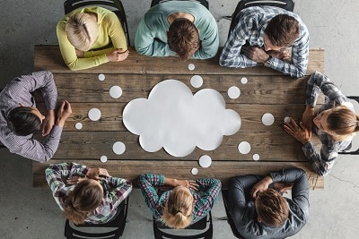 People sit around a table with a ideas cloud